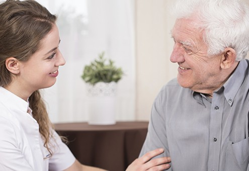 Senior smiling male pensioner and his pretty young caregiver