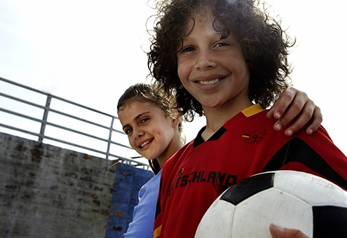 Portrait of boy (10-11) and girl (10-11) with soccer ball