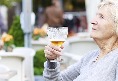 Happy active senior woman relaxing in outdoors cafe