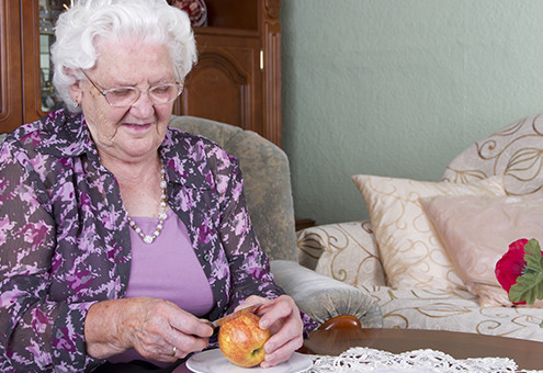 Photo shows a Grandma. She is peeling a apple. Studiolight.